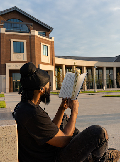 student reading in front of student center