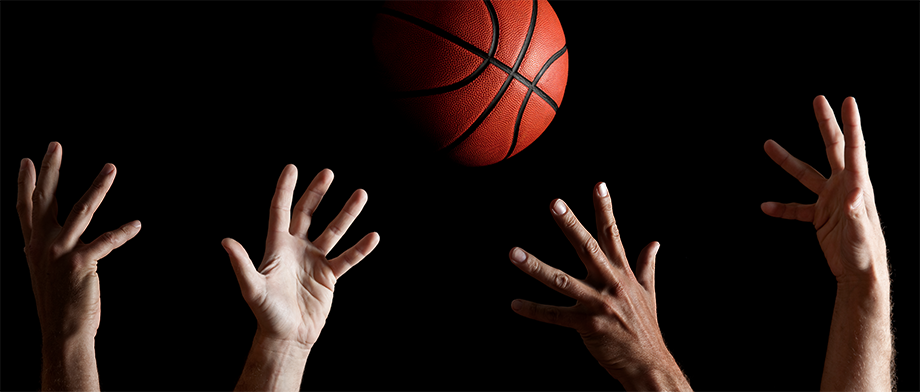 basketball with hands reaching up